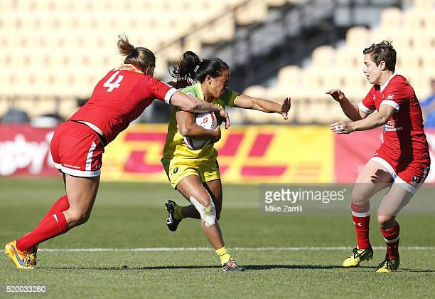 Amy Turner of Australia runs with the ball and attempts to avoid being tackled by Kelly Russell and Ghislaine Landry of Canada during the match at...