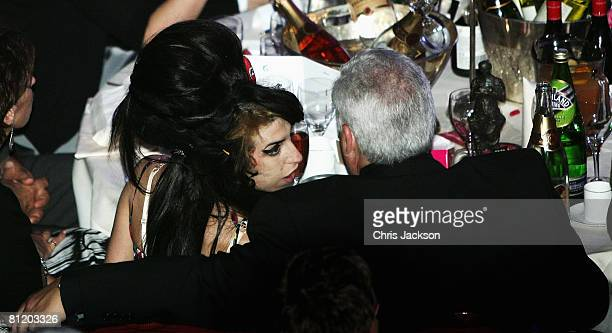 Amy Winehouse and her dad Mitch Winehouse chat during the 53rd Ivor Novello Awards after she won Best Song Musically and Lyrically at the Dorchester...
