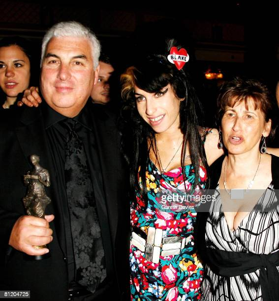 Amy Winehouse her father Mitch and mother Janis pose with Amy's award for Best Song Musically and Lyrically for 'Love Is A Losing Game' at the 53rd...