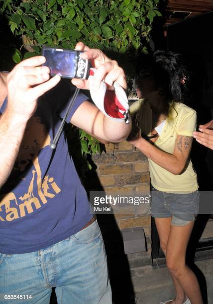 Amy Winehouse returns home from the Proud Camden pub and when one of her fans approaches her for a photograph she viciously swings her fist toward...