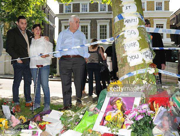 Amy Winehouse's brother Alex Winehouse mother Janis Winehouse and father Mitch Winehouse look at the floral tributes left outside her Camden Square...