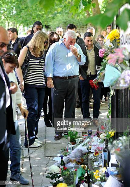Amy Winehouse's father Mitch Winehouse and Amy's brother Alex Winehouse look at floral tributes left at her house by fans on July 25 2011 in London...
