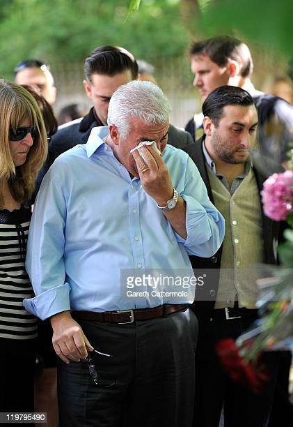 Amy Winehouse's father Mitch Winehouse and brother Alex Winehouse look at floral tributes left at her house by fans on July 25 2011 in London England