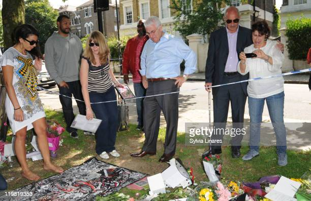 Amy Winehouse's father Mitch Winehouse and mother Janis Winehouse are seen looking at the floral tributes outside her Camden Square home on July 25...