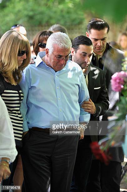 Amy Winehouse's father Mitch Winehouse brother Alex Winehouse and Amy's former boyfriend Reg Traviss look at floral tributes left at her house by...