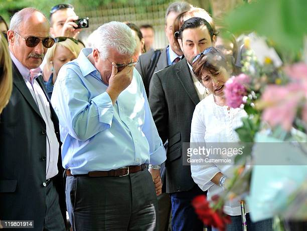 Amy Winehouse's father Mitch Winehouse brother Alex Winehouse and her mother Janis Winehouse look at floral tributes left at her house by fans on...