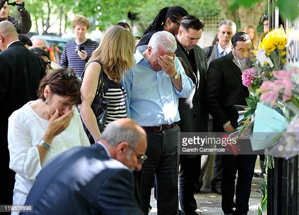 Amy Winehouse's father Mitch Winehouse brother Alex Winehouse her former boyfriend Reg Traviss and her mother Janis Winehouse look at floral tributes...