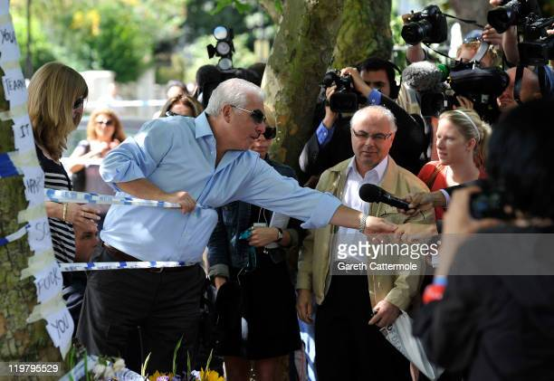 Amy Winehouse's father Mitch Winehouse greets a fan of his daughter as he looks at floral tributes left at her house by fans on July 25 2011 in...