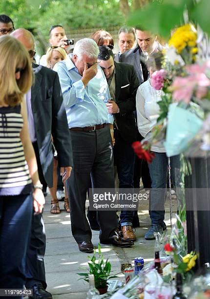 Amy Winehouse's father Mitch Winehouse is comforted by his son Amy's brother Alex Winehouse as they look at floral tributes left at her house by fans...