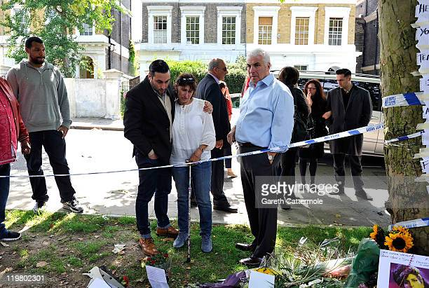 Amy Winehouse's father Mitch Winehouse mother Janis Winehouse and brother Alex Winehouse look at floral tributes left at Amy's house by fans on July...