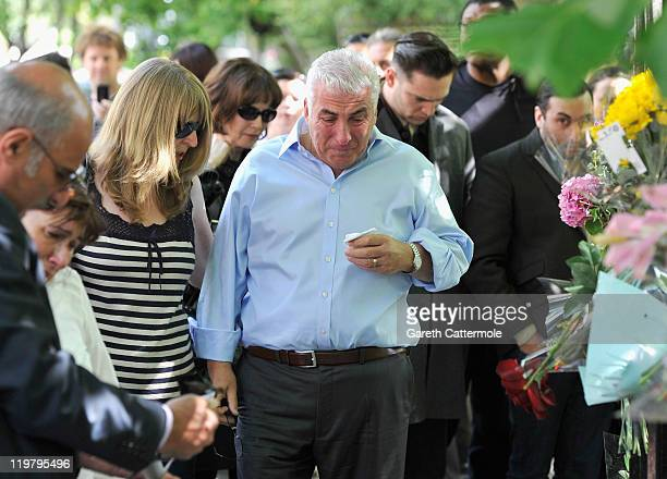 Amy Winehouse's father Mitch Winehouse mother Janis Winehouse brother Alex Winehouse and former boyfriend Reg Traviss look at floral tributes left at...