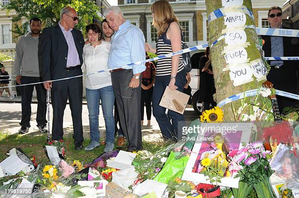 Amy Winehouse's mother Janis Winehouse brother Alex Winehouse and father Mitch Winehouse look at the floral tributes left outside her Camden Square...