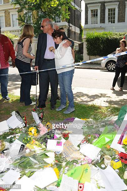 Amy Winehouse's mother Janis Winehouse is comforted as she looks at the floral tributes left outside her Camden Square home on July 25 2011 in London...
