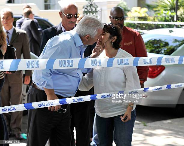 Amy Winehouse's mother Janis Winehouse shares a kiss with Amy's father Mitch Winehouse as they look at floral tributes left at her house by fans on...
