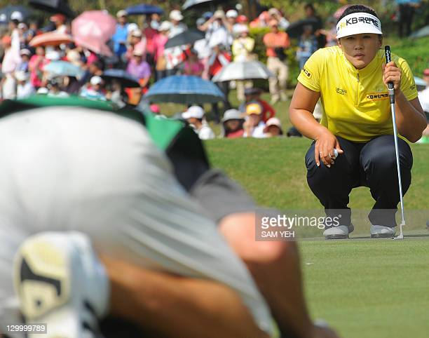 Amy Yang of South Korea lines up a putt with her caddie on the eigth green during the forth round of the Sunrise LPGA Taiwan Championship golf...
