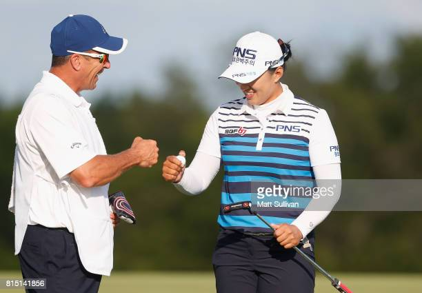 Amy Yang reacts with her caddie Greg Johnston after making a birdie on the 17th hole during the third round of the US Women's Open Championship at...