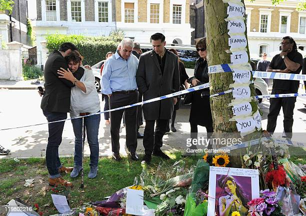 Amy's father Mitch Winehouse and mother Janis Winehouse look at floral tributes with Amy's former boyfriend Reg Traviss at Amy's house on July 25...