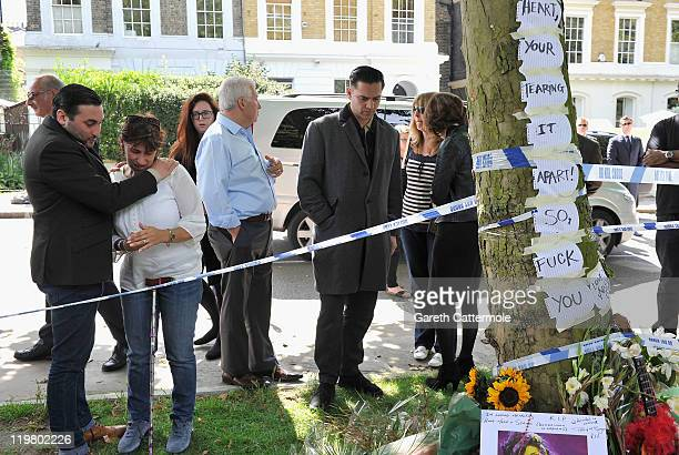 Amy's father Mitch Winehouse and mother Janis Winehouse look at floral tributes with theri son Alex Winehouse Amy's former boyfriend Reg Traviss at...