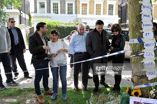 Amy's father Mitch Winehouse and mother Janis Winehouse look at floral tributes with their son Alex Winehouse and Amy's former boyfriend Reg Traviss...