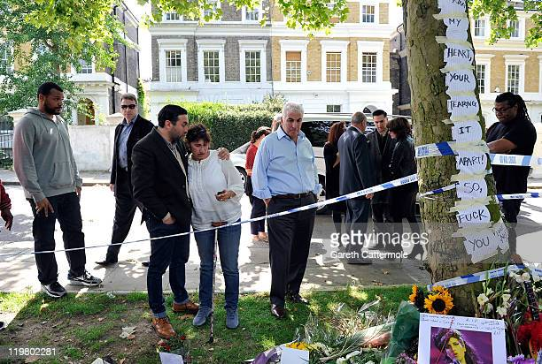 Amy's father Mitch Winehouse and mother Janis Winehouse look at floral tributes with their son Alex Winehouse at Amy's house on July 25 2011 in...