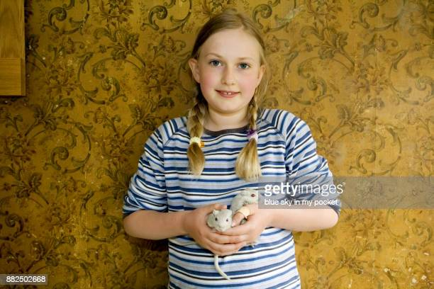 An 11 year old girl holding some pet Gerbils.