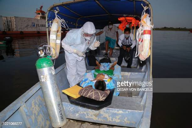 An 11-year-old COVID-19 patient arrives on a boat from a nearby community at a port in the Amazon River, in Iquitos, Loreto region, Peru, on June 18...
