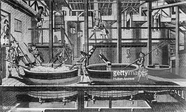 An 18th century brew house with workers stirring the brew which is in large vats in the foreground In the background are large brick built kilns for...
