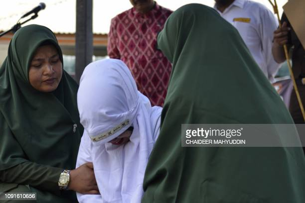 An 18yearold Indonesian woman is assisted by Sharia police after being caned in public in Banda Aceh on January 31 as punishment for being caught...