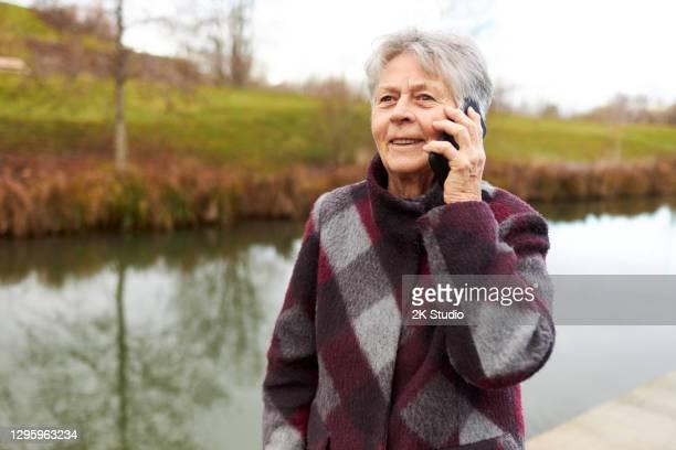 een 80-jarige oudere vrouw gebruikt haar smartphone voor videotelefonie en om te navigeren tijdens de wandeling - alleen één seniore vrouw stockfoto's en -beelden