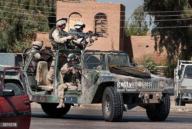 An 82nd Airborne Division1st battalion 504th regiment humvee patrol blocks traffic for an October 9 2003 convoy turning off a highway near the Abu...