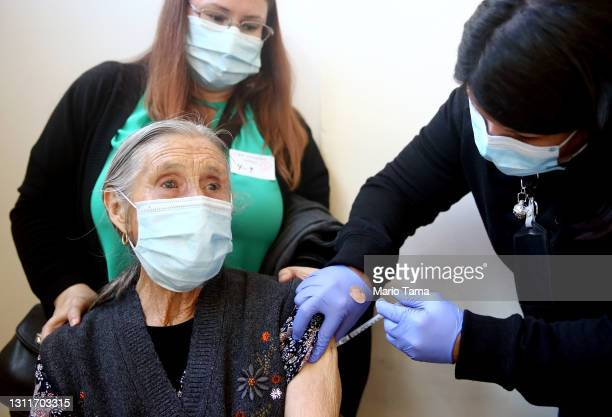 An 86-year-old woman receives her first dose of the Pfizer COVID-19 vaccine at a clinic targeting minority community members at St. Patrick's...