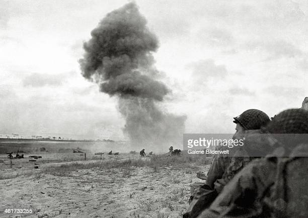 An 88 mm shell explodes on Utah Beach 6th June 1944 In the foreground US soldiers protect themselves from enemy fire Normandy France