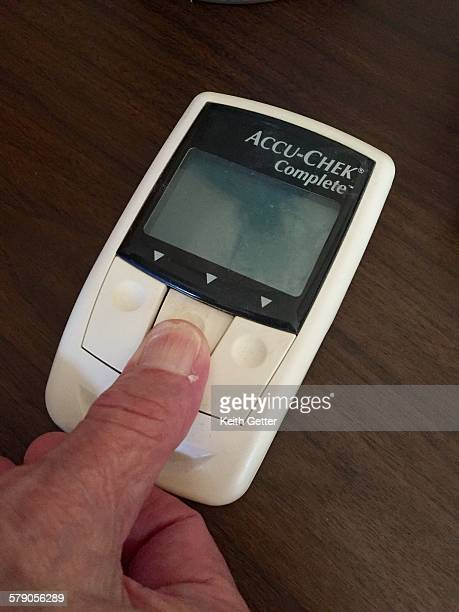 An 88 year old man at his home pushing one of the buttons on a blood glucose monitoring device to turn on the meter