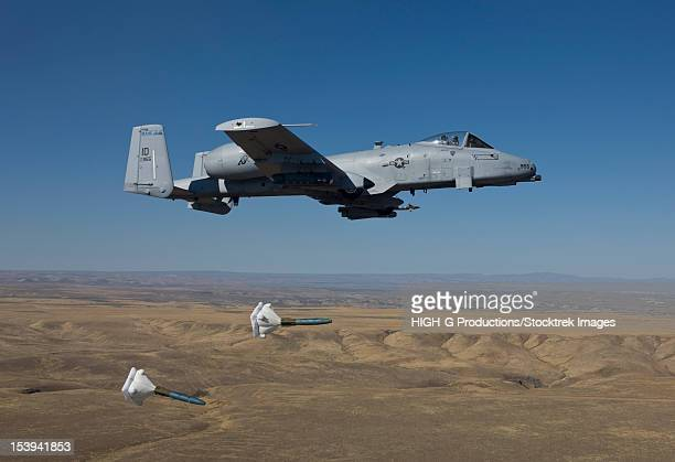 an a-10c thunderbolt from the 190th fighter squadron releases two high drag bdu-50's during a training mission out of boise, idaho. - military attack stock pictures, royalty-free photos & images