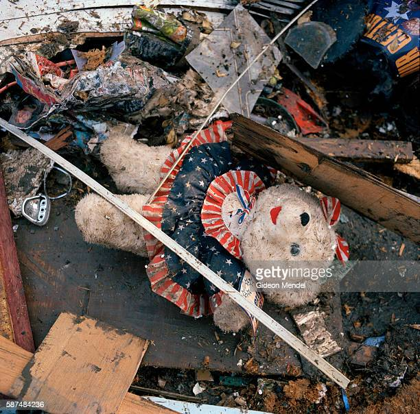 An abandoned and flood damaged teddy bear wearing a dress patterned on the Australian flag lies on top of one of the many piles of flood damaged...
