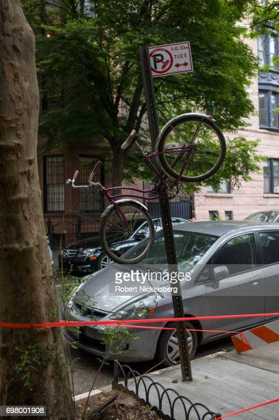 An abandoned bicycle hangs from a traffic sign post June 13, 2017 in the Brooklyn borough of New York City. Contractors later lowered the bicycle...
