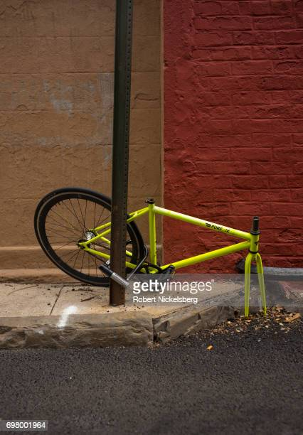 An abandoned bicycle hangs from a traffic sign post June 16, 2017 in the Brooklyn borough of New York City. The bicycle's parts have been stolen over...