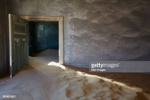 An abandoned building, an open door and drifts of sand encroaching into the room from the rest of the building. A ghost town.