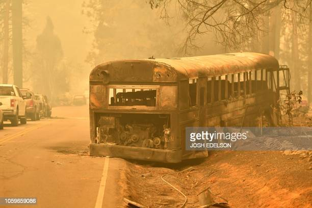An abandoned burned-out school bus sits on the side of a road in Paradise, north of Sacramento, California on November 09, 2018. - A rapidly...