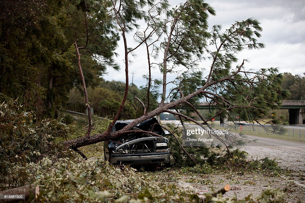 An abandoned car damaged by a fallen tree sits along Interstate 16, October 8, 2016 in Savannah, Georgia. Across the Southeast, Over 1.4 million people have lost power due to Hurricane Matthew which has been downgraded to a category 1 hurricane on Saturday morning.