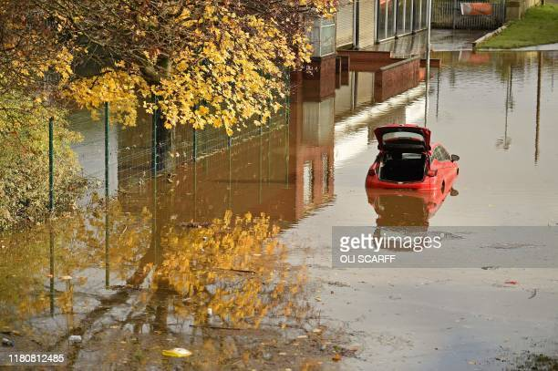 An abandoned car is pictured submerged in flood water in Rotherham northern England on November 8 following flash flooding yesterday Over a month's...