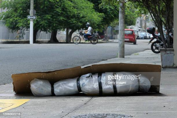 An abandoned corpse wrapped in plastic and covered with cardboard lies on the sidewalk near the intersection of Maracaibo and Buenos Aires streets on...