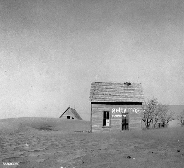 An abandoned farmhouse in Oklahoma sits amid piles of sand during the Dust Bowl of the 1930s.