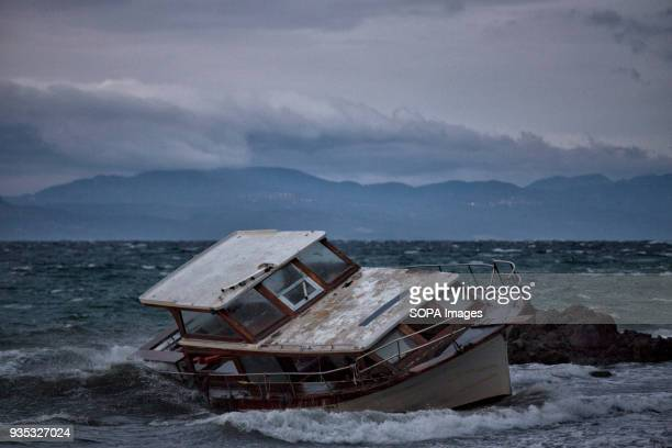 An abandoned fishing boat on the shoreline left by asylumseekers and refugees arriving in Greece In 2015 more than a million immigrants arrived in...