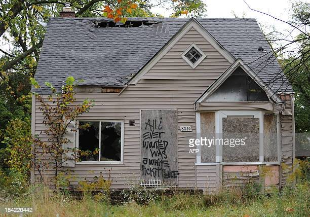 """An abandoned home seen September 30, 2013 in Detroit, Michigan, is decorated with a piece of fencing and graffiti which declares """"All I ever wanted..."""