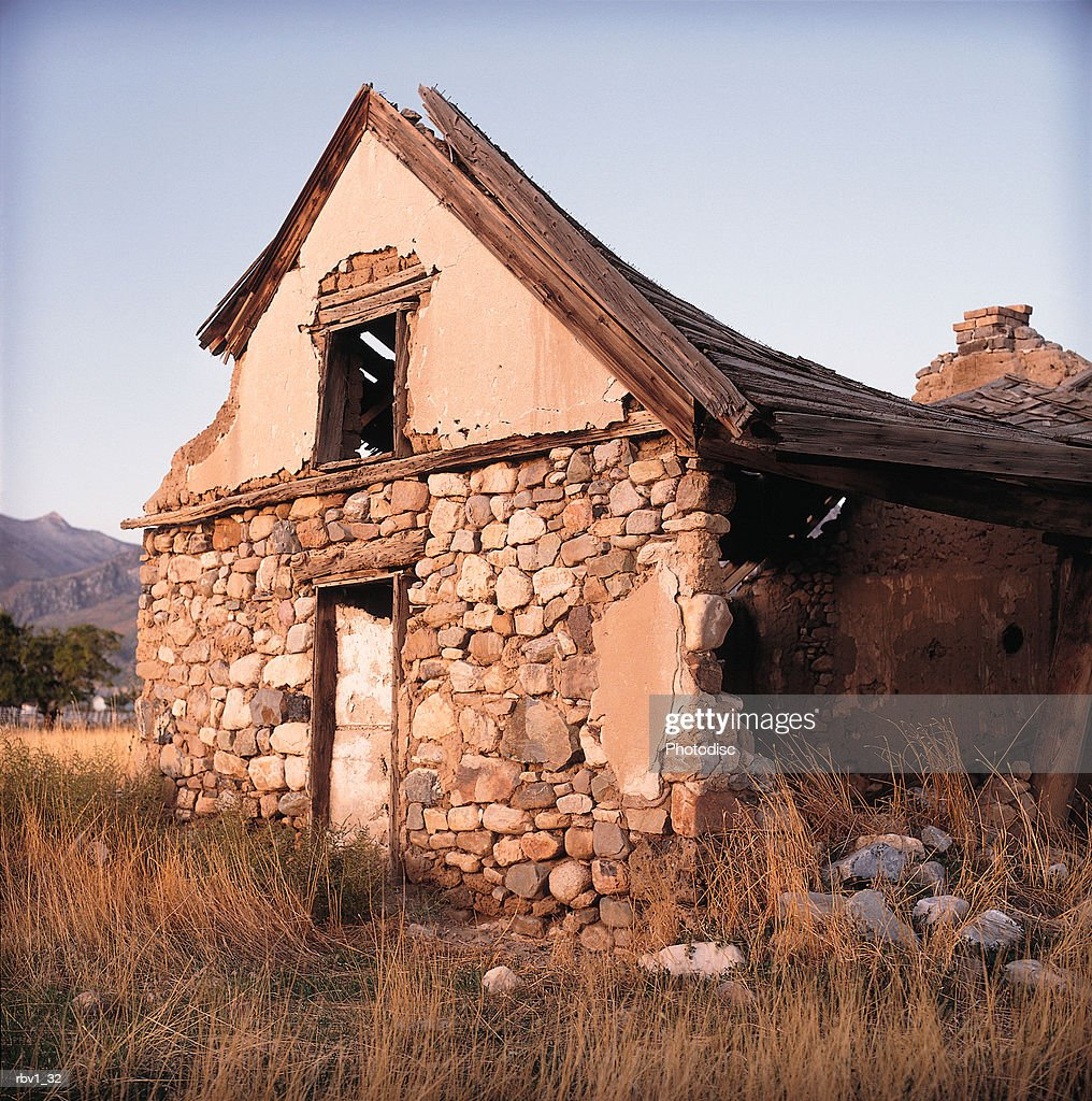 an abandoned house made of wood and stone stands alone falling apart under a blue sky with trees and mountains in the background : Foto de stock