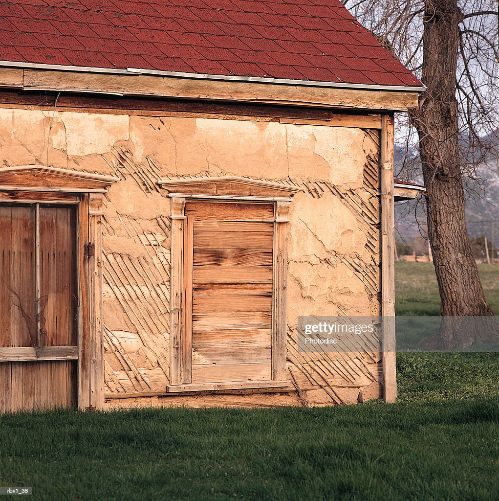 an abandoned house with red shingles and a boarded up doorway and window sits among green grass and trees with the mountains in the distance : Foto de stock