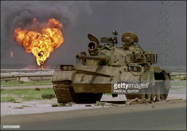 An abandoned Iraqi Sovietmade T62 tank sits in Kuwaiti desert 02 April 1991 as an oil well at the AlAhmadi oil field is burning in the background In...