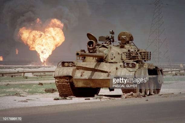 An abandoned Iraqi Sovietmade T62 tank sits in Kuwaiti desert on April 2 1991 as an oil well at the AlAhmadi oil field is burning in the background...