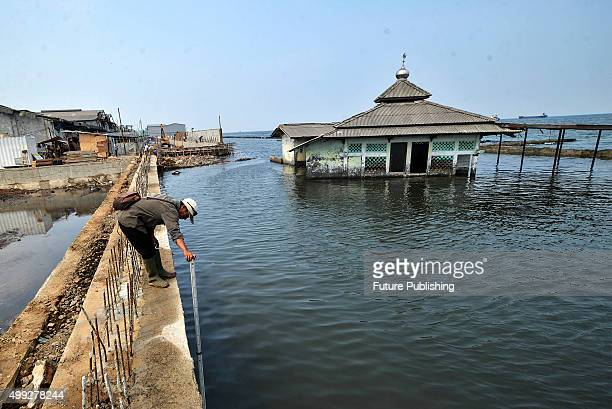 An abandoned mosque which has been surrounded by the encroaching sea sits in the Maura Baru district seen on November 30 2015 in Jakarta Indonesia...